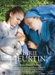 Affiche du film Marie HEURTIN. On y voit les deux actrices qui jouent le rôle de Marie et de Soeur Marguerite allongées dans l'herbe et qui se tiennent par la main.