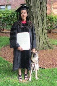 Photo de Haben GIRMA en tenu de remise de diplome américain (grande robe noir semble à celles des avocats en France), tenant son diplôme à la main. Son chien guide se tient assis à côté d'elle.