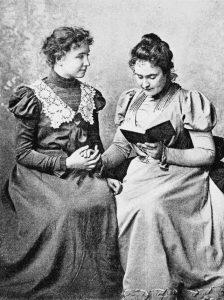 Photo d'Helen KELLER et Ann SULLIVAN. Ann lit un livre à Helen en dactylologie tactile
