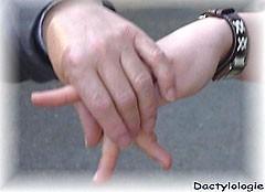 Photo illustrant la dactylologie tactile, on y voit une main qui fait une lettre en alphabet lsf et une autre main posée dessous pour sentir la lettre